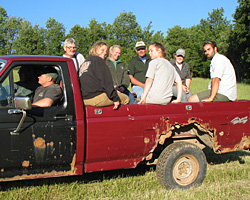 Interns from several farms being are in a classic farm truck heading to a workshop.